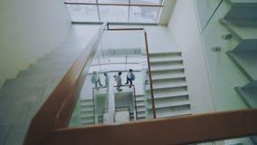 La opinión superior dos hombres de negocios se encuentra en las escaleras en centro moderno y hablar de la oficina mientras que t