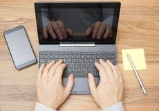 La opinión superior el hombre da el trabajo en la PC del ordenador portátil o de la tableta en d de madera Fotos de archivo libres de regalías