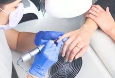 La opinión superior el manicuro en guantes de goma azules y máscara médica limpia la cutícula en clavos femeninos usando una fres imagen de archivo