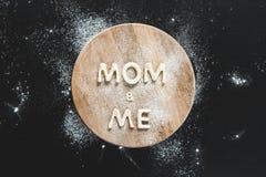 La opinión superior la mamá y mí comestibles de las letras hizo de las galletas en tabla de cortar de madera Fotos de archivo libres de regalías