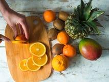La opinión superior la mujer da cortar naranjas frescas con el cuchillo Hembra que hace la ensalada de fruta fresca Concepto vege foto de archivo libre de regalías