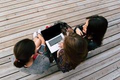La opinión superior las mujeres de un árbol que se sientan con el ordenador portátil y el teléfono móvil con la copia en blanco e Imagenes de archivo