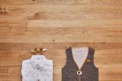La opinión superior los niños forma la ropa con los accesorios en el fondo de madera Imagen de archivo libre de regalías