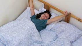 La opinión superior la muchacha soñolienta despierta y estira acostarse con una manta blanca por la mañana metrajes