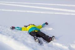 La opinión superior la muchacha sonriente linda que miente en nieve muestra ángel Foto de archivo libre de regalías