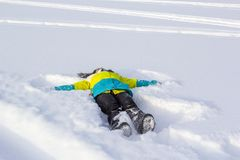 La opinión superior la muchacha sonriente linda que miente en nieve muestra ángel Fotos de archivo