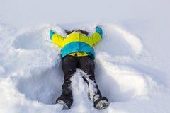 La opinión superior la muchacha sonriente linda que miente en nieve muestra ángel Imagen de archivo libre de regalías