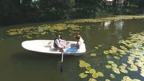 La opinión superior sobre pares está flotando en un barco en el lago en madera almacen de metraje de vídeo