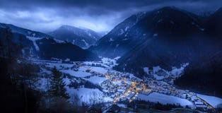 La opinión superior sobre pueblo nevoso luesen el valle en la noche el Tirol del sur él fotos de archivo