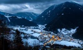 La opinión superior sobre pueblo nevoso luesen el valle en la noche el Tirol del sur él imágenes de archivo libres de regalías