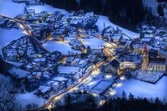 La opinión superior sobre pueblo nevoso luesen el valle en la noche el Tirol del sur él foto de archivo