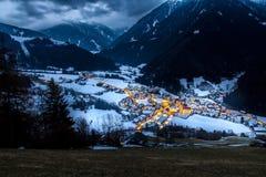 La opinión superior sobre pueblo nevoso luesen el valle en la noche el Tirol del sur él imagenes de archivo