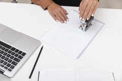 La opinión superior una mujer en blusa marrón está utilizando un sello fotografía de archivo