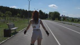 La opinión trasera la chica joven bonita en pantalones cortos y tops patina en pcteres de ruedas Fotos de archivo libres de regalías