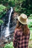 La opinión trasera la chica joven de lejos admira la cascada Fotos de archivo libres de regalías