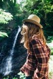 La opinión trasera la chica joven de lejos admira la cascada Foto de archivo libre de regalías