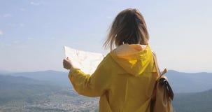 La opinión trasera el caminante femenino caucásico en impermeable amarillo se coloca en las montañas con un mapa a disposición metrajes
