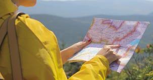 La opinión trasera el caminante femenino caucásico en impermeable amarillo se coloca en las montañas con un mapa a disposición almacen de metraje de vídeo