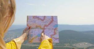 La opinión trasera el caminante femenino caucásico en impermeable amarillo se coloca en las montañas con un mapa a disposición almacen de video