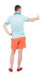 La opinión trasera el hombre en pantalones cortos muestra los pulgares para arriba Foto de archivo libre de regalías