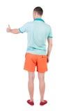 La opinión trasera el hombre en pantalones cortos muestra los pulgares para arriba Imagen de archivo libre de regalías