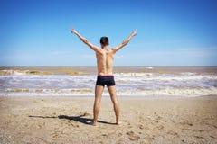 La opinión trasera el hombre joven se separó las manos en la playa Foto de archivo