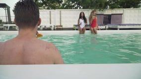 La opinión trasera el individuo joven mojado getted hacia fuera de la piscina al aire libre en el fondo de dos muchachas hermosas almacen de video