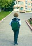 La opinión trasera el pequeño colegial con una mochila va a la escuela outdoor Educación, de nuevo a concepto de la escuela imágenes de archivo libres de regalías