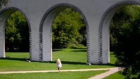 La opinión trasera escénica la mujer joven camina en el parque con los arcos grandes metrajes