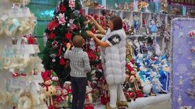 La opinión trasera integral la madre y el hijo alegres que adornan el árbol de navidad en el centro comercial almacen de metraje de vídeo