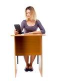 La opinión trasera la mujer se sienta por la tabla y mira la pantalla de Imagenes de archivo