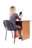 La opinión trasera la mujer se sienta por la tabla y mira la pantalla de Imagen de archivo