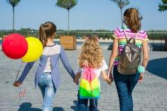 La opinión trasera las colegialas de los niños que llevan a cabo las manos camina junta encendido Fotos de archivo libres de regalías