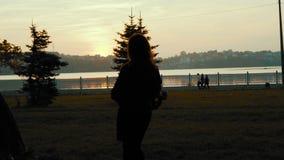 La opinión trasera la muchacha camina con confianza con la bufanda en manos en parque 4K metrajes
