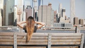 La opinión trasera la muchacha feliz con el pelo largo del vuelo que goza sorprendiendo la opinión del horizonte de Manhattan que almacen de metraje de vídeo