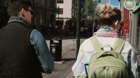 La opinión trasera turistas jovenes junta caminar en centro de ciudad y la exploración de las vistas Hombre y mujer fecha románti almacen de metraje de vídeo