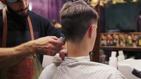 La opinión trasera un cliente que conseguía su pelo cortó por un peluquero El peluquero barbudo está cortando el pelo usando el c almacen de video
