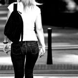 La opinión trasera una muchacha que camina abajo de la calle Rebecca 36 Imagen de archivo