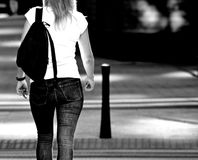La opinión trasera una muchacha que camina abajo de la calle Rebecca 36 Fotos de archivo libres de regalías
