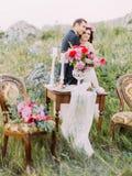 La opinión vertical los recienes casados de abrazo detrás del sistema borroso de la tabla que se casa Fotografía de archivo libre de regalías