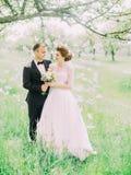 La opinión vertical preciosa los recienes casados felices que se colocan en el frente de los cisnes de papel que cuelgan en el ár Foto de archivo