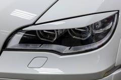 La opini?n delantera del faro del coche usado blanco se coloca en la venta auto de la sala de exposici?n despu?s del lavado y el  foto de archivo libre de regalías