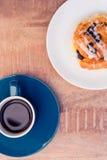 La opinión de alto ángulo de la comida dulce sirvió en placa por la taza de café en la tabla Foto de archivo
