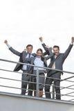 La opinión de ángulo bajo empresarios emocionados con los brazos aumentó en terraza contra el cielo Imagenes de archivo