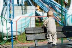 La opinión trasera el bebé que mira el carrusel en atracciones parquea Foto de archivo