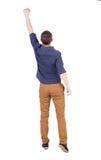 La opinión trasera el hombre en camisa a cuadros aumentó su puño para arriba en victo Imágenes de archivo libres de regalías