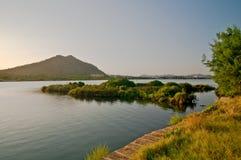 La orilla del lago y una pequeña isla en la puesta del sol se encienden Foto de archivo