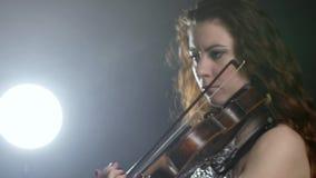 La orquesta sinfónica, muchacha está jugando en el instrumento musical en la iluminación del reflector metrajes