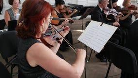 La orquesta sinfónica, violinistas con las notas juega en sus instrumentos musicales dentro almacen de metraje de vídeo