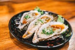 La ostra jugosa cruda tres se abrió y sirvió recientemente en plato en el restaurante japonés Menú famoso de los mariscos frescos imagen de archivo